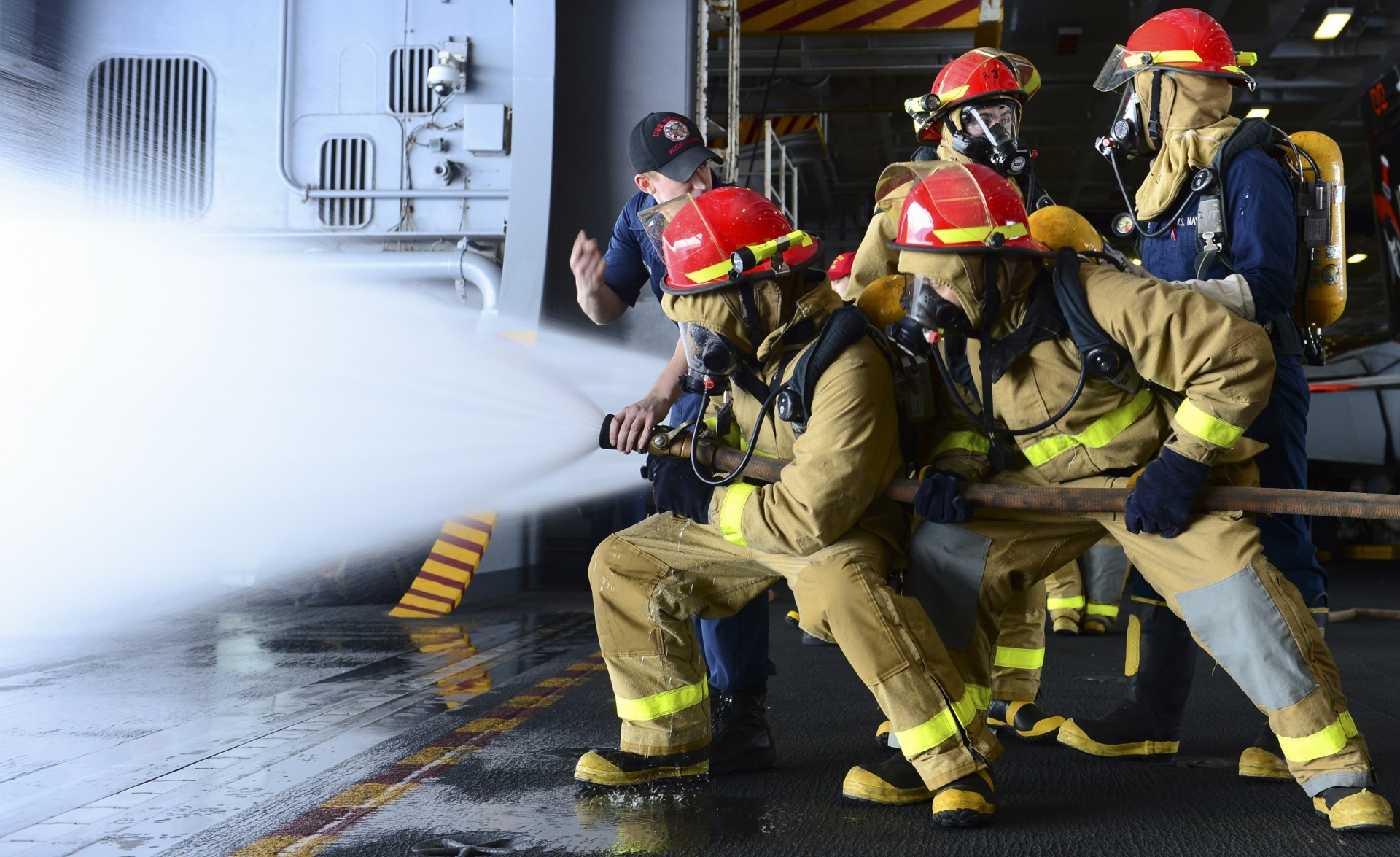 Four US Navy firefighters handling a full pressure firehose as an instructor directs them.